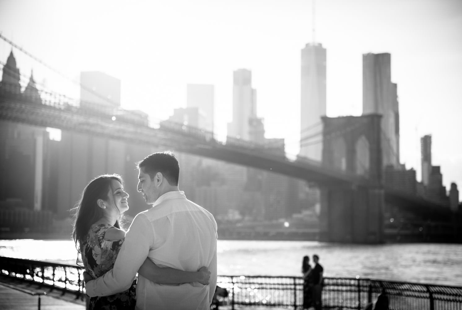 Couple standing in front of a bridge