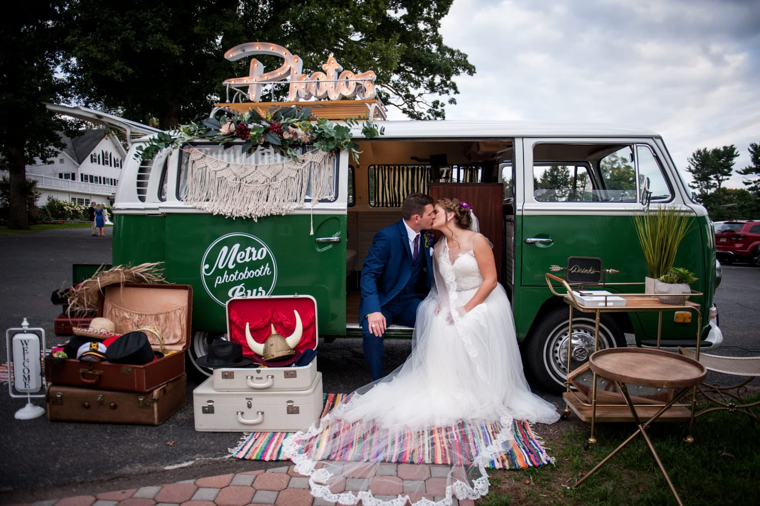 Bride and groom sitting by a vintage Volkswagen photo booth kissing
