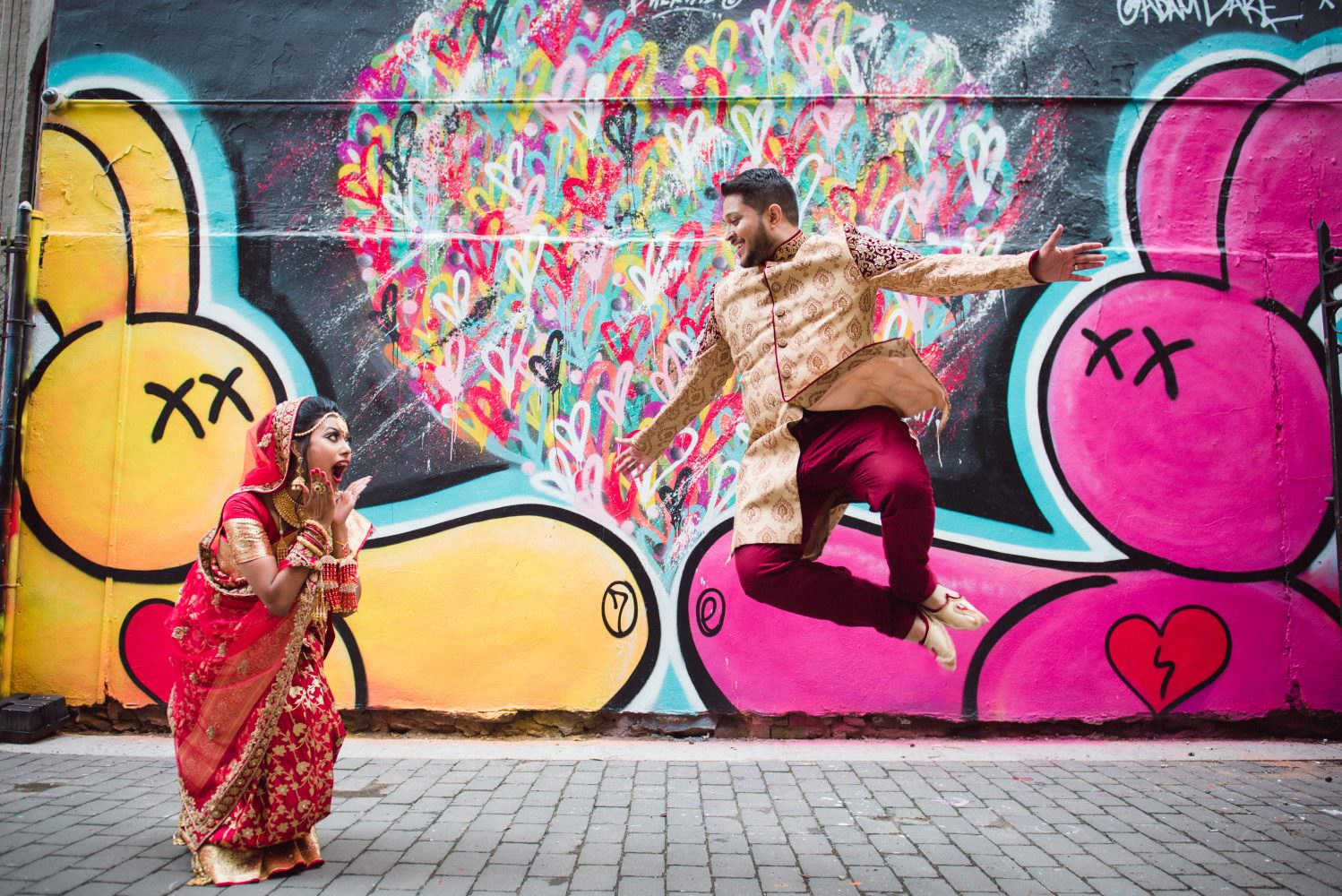Bride and groom jumping next to a Graffiti on a wall