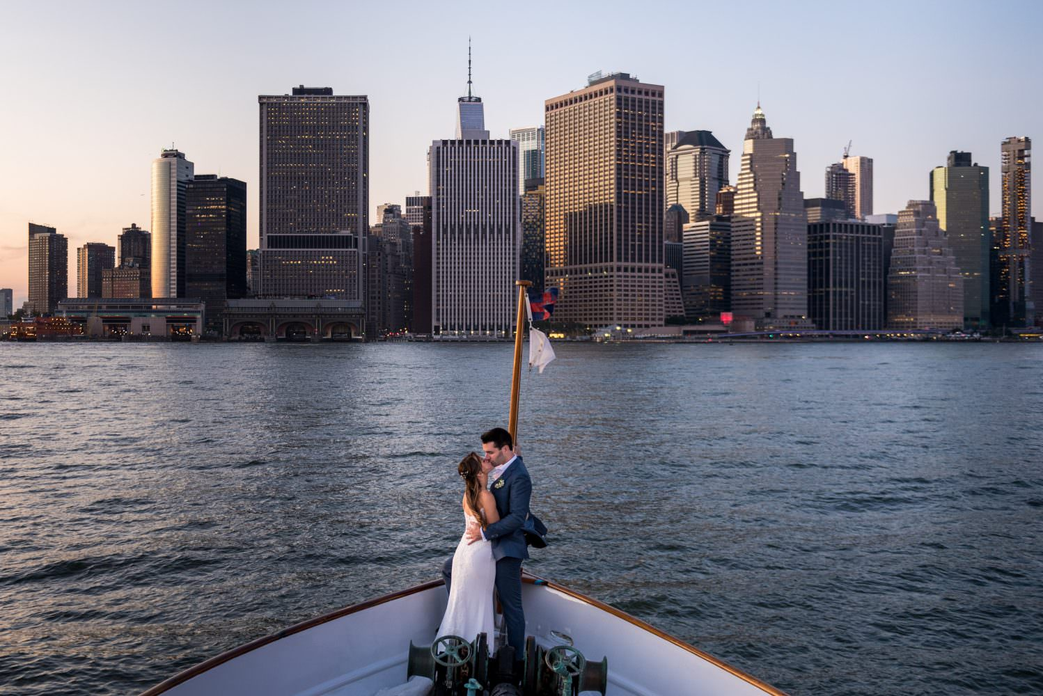 A couple kissing by a body of water with a city in the background