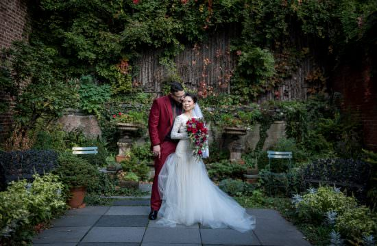 Bride and groom posing for portrait in a garden