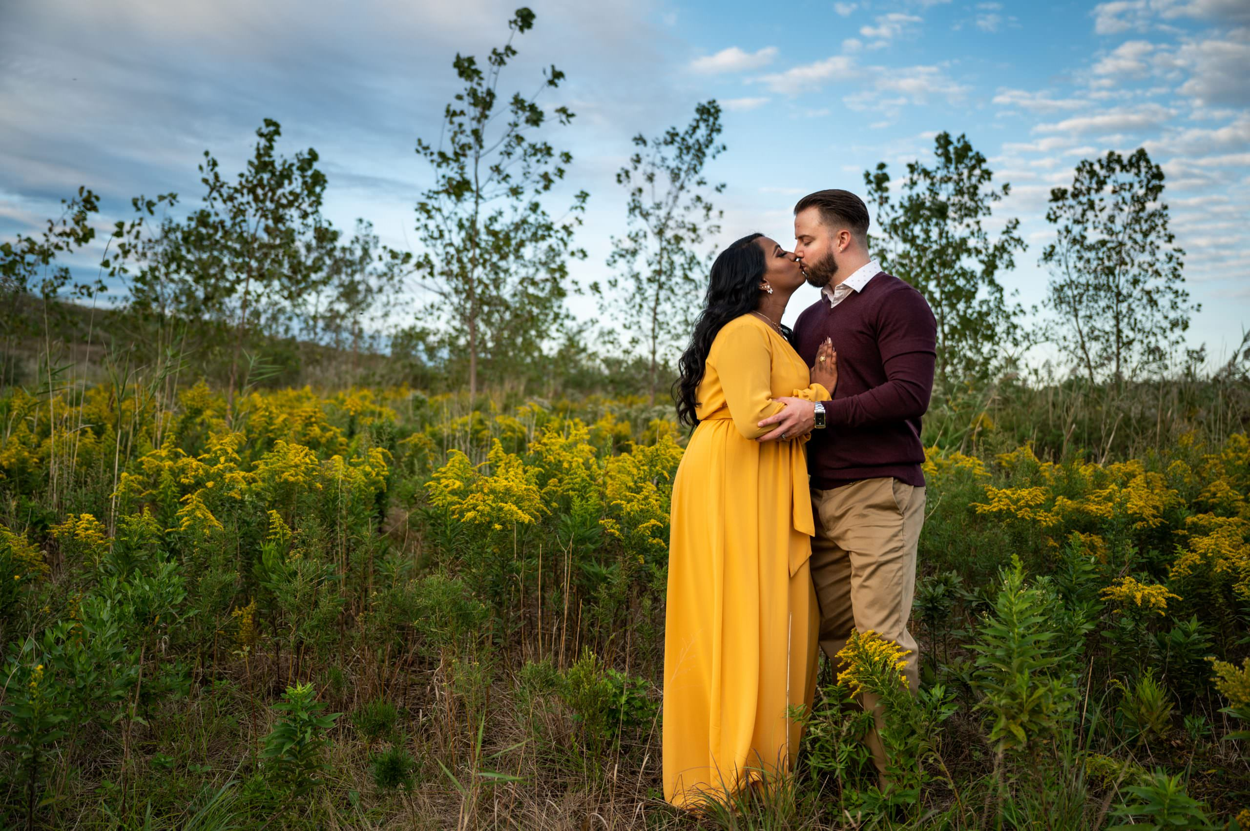 A couple kissing by a body of flowers with the open sky in the background